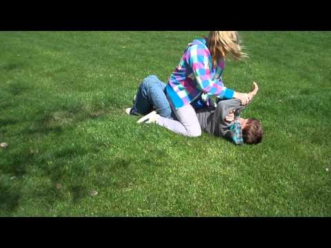 Sister pins brother on grass