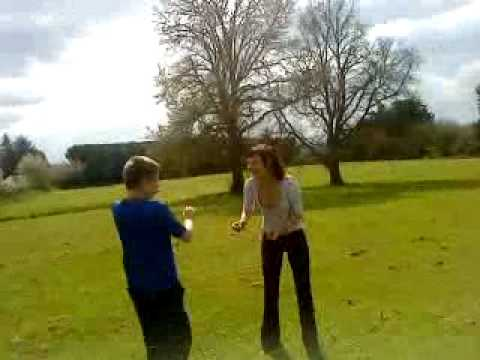 Girl pins boy on grass